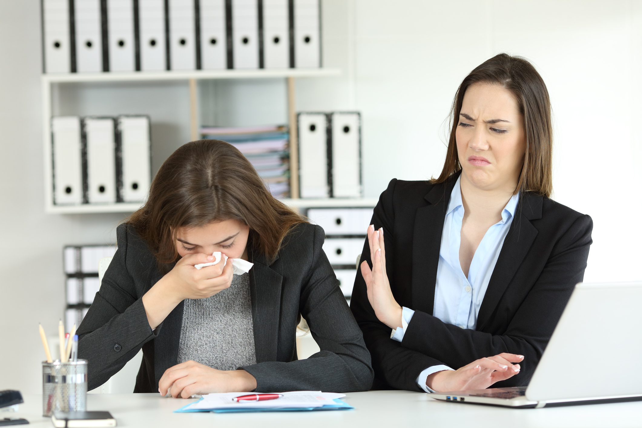 Woman sneezing in office beside co-worker who is trying to move away