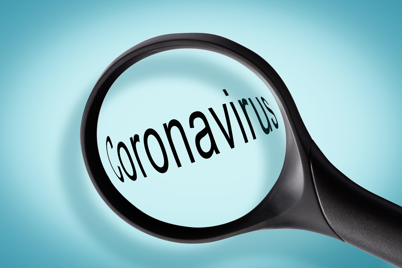 Illustration of a magnifying glass examining the word 'coronavirus'