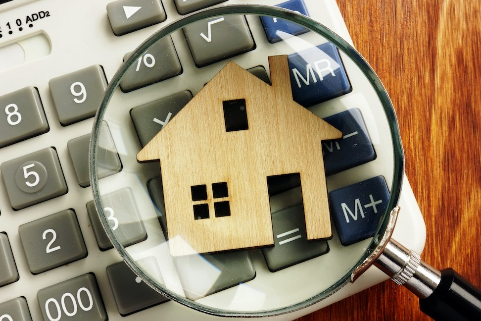 Model house examined with magnifying glass with calculator