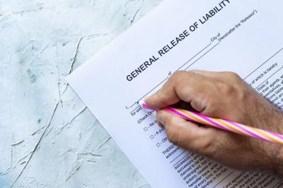 Hand signing a general release of liability form