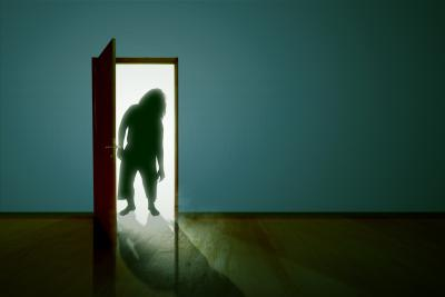 Silhouette of Zombie standing at an open door