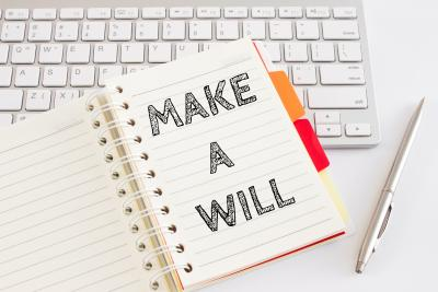 Notebook lying on keyboard with word 'make a will' written on it.